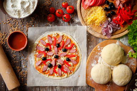 Pizza dough with ingredients on wood, shot from above Stock fotó