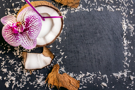 coconuts with coconuts flakes and orchid on the grey stone background