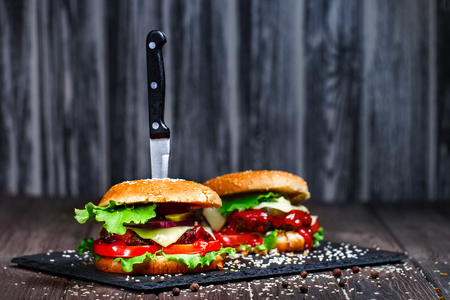 Closeup of mouth-watering, delicious homemade burgers with volatile, onions, ketchup, tomatoes, served with a knife stuck on stone board. Stok Fotoğraf