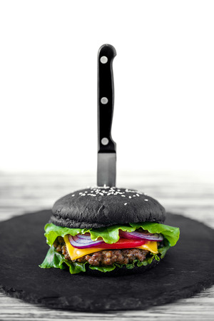 Close up of Homemade Black Burger with Cheese. Cheeseburger with black bun on white wooden background. Junk food. Stock fotó