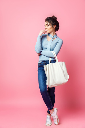 Cheerful casual young woman with bag looking away on pink background.