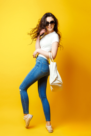 Beautiful young woman in sunglasses, white shirt, blue jeans posing with bag on the yellow background Foto de archivo