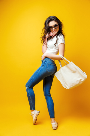 Beautiful young woman in sunglasses, white shirt, blue jeans posing with bag on the yellow background Banco de Imagens