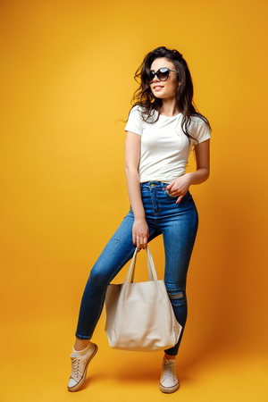 Young brunette woman in sunglasses with bag standing on yellow background.