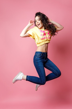 Pretty young woman in casual clothes jumping on pink background.