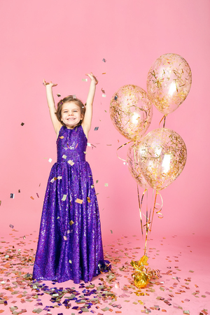 Happy young girl in purple glittering dress celebrating with hands up and smile on pink background.
