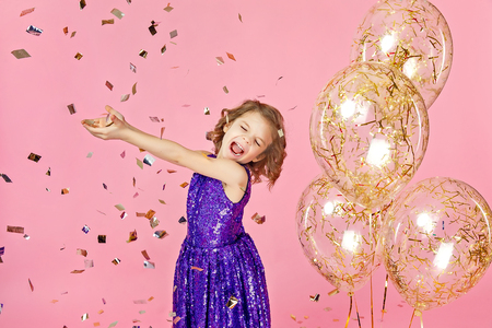 Happy young girl in purple glittering dress celebrating with hands up and smile or skreaming with joy while cathcing confetti, having fun on pink background.