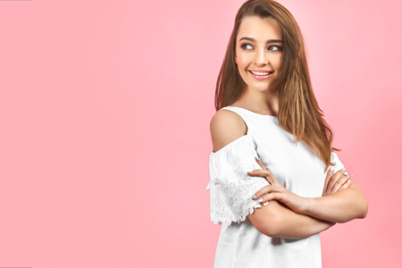 Beautiful girl wearing white dress and posing on pink background. Moving and looking away from camera. Beautiful hairstyle and makeup. Isolate.