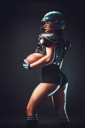 Sportieve ernstige vrouw in helm van de holdingsbal van de rugbyspeler in stuio op donkere achtergrond.
