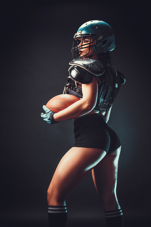 Sportive serious woman in helmet of rugby player holding ball in stuio on dark background.