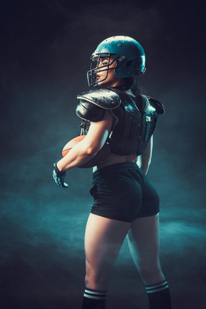 Sportive serious woman in helmet of rugby player holding ball in stuio on dark background. Side view, smoke