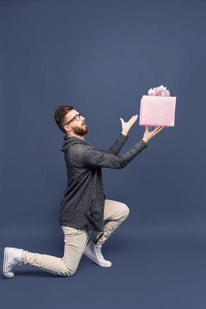 Side view of content expressive man standing on knee offering pink present dramatically.