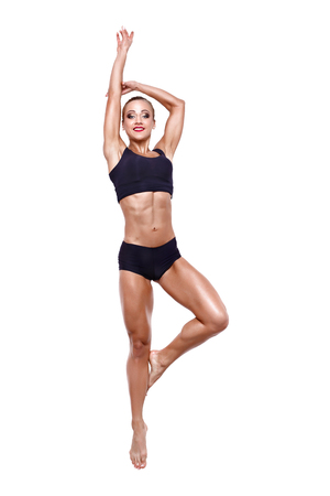 Fitness woman jumping excited isolated on white background. Full body image of beautiful Caucasian female model in jump flexing and showing muscles.