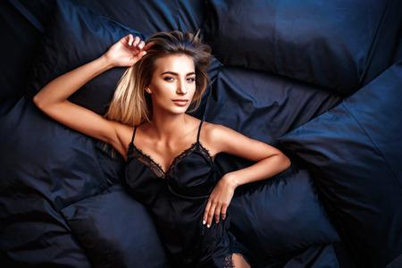 Modefoto der sexy Zauberfrau mit dem blonden Haar, welches die elegante Spitzewäsche, liegend auf schwarzem silk Bett trägt. Ansicht von oben