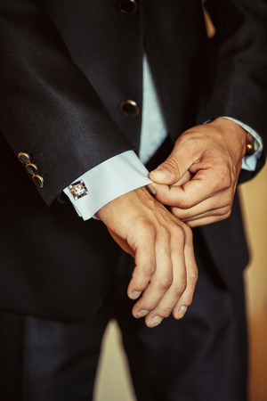 Unknown manfastens the cuffs of his shirt. Morning of the groom.The groom fastens the cuff links to the cuffs of the shirt while gathering on their wedding day.Businessman fastens cuff