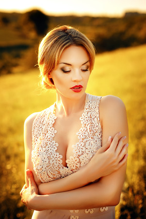 fashion photo of beautiful young girl with blond hair wearing luxurious beige dress on sunset.