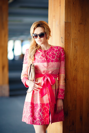 fashion photo of beautiful young girl with blond hair wearing luxurious pink dress, bag at underground parking.