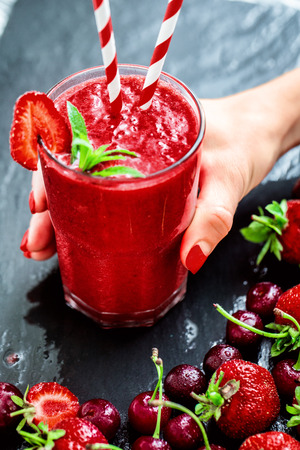 Woman hand holding Glass with two straws filled with strawberry smoothie on black with strawberries.