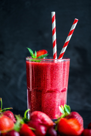 Glass with two straws filled with strawberry smoothie on black with strawberries. Stock Photo