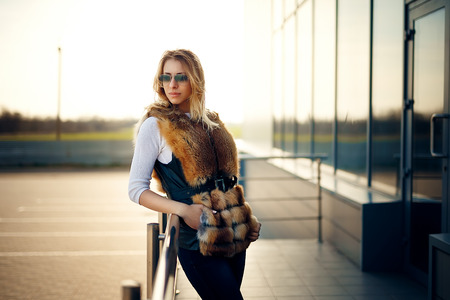 Beautiful blonde woman outdoors in a fur vest and sunglasses
