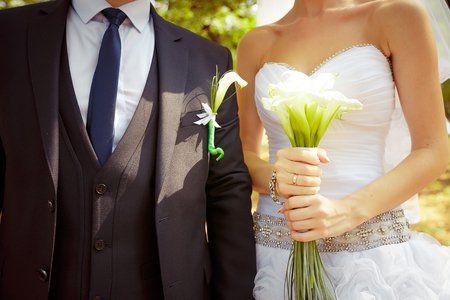 Bride holding beautiful white wedding flowers bouquet. groom standing behind with same flowers in boutonniere Stock Photo