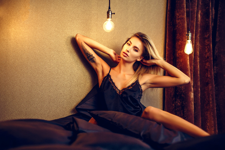 fashion photo of glamour woman with blonde hair wearing elegant lace lingerie, lying on black silk bed.