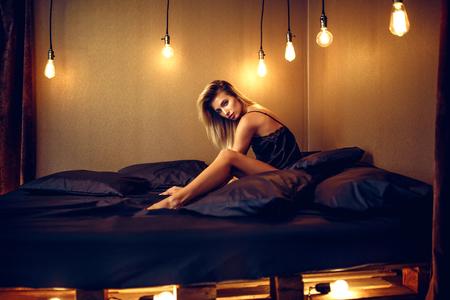 mode foto van sexy glamour vrouw met blond haar, gekleed in elegante kanten lingerie, liggend op zwart zijden bed.