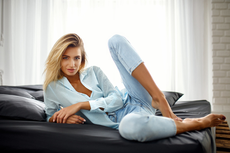 Natural pretty blonde girl in casual clothes sitting on bed in bright bedroom