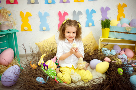 Charming girl sitting with yellow soft chiken in hands looking at camera and smiling in Easter decoration.