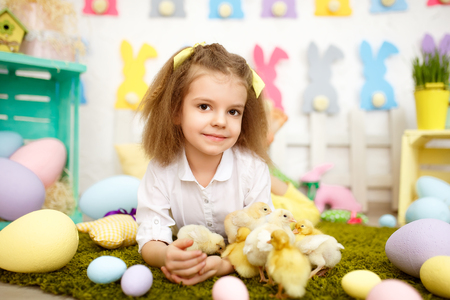 Wonderful little girl lying on green meadow in studio with plenty of soft yellow ducklings and chickens walking around in Easter decoration.