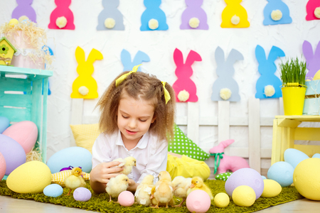 Little innocent girl in bows lying on green lawn with eggs and playing with yellow small ducklings and chickens in Easter decoration.