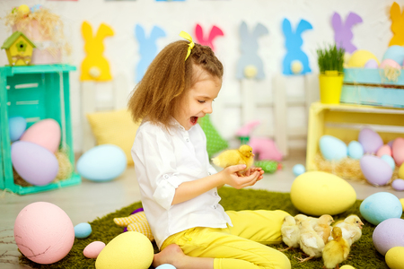 Charming content girl with yellow bows playing with small duckling among decorative eggs for Easter.