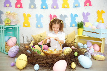 Little charming girl with yellow bows holding basket full of fluffy tiny ducklings and chikens with smile in Easter decoration.