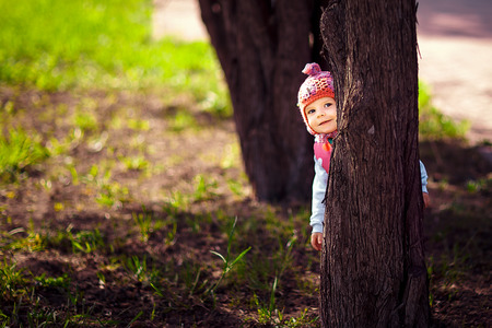 small child plays Spring Park, hiding behind a tree