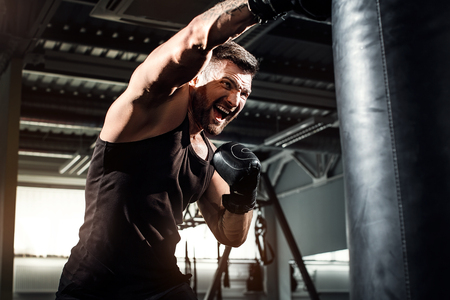 Bearded Male boxer training with punching bag in dark sports hall. Young tattoed boxer training on punching bag. Male boxer as exercise for the big fight. Boxer hits punching bag. Stock Photo