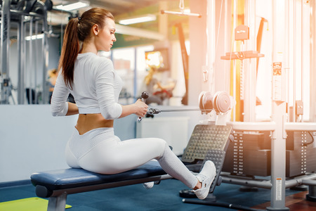 Young Woman training back with weight-lifting training machine
