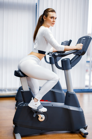 Indoor cycling woman doing HIT cardio workout biking on indoors gym bike. Girl cyclist working out interval training on bicycle.