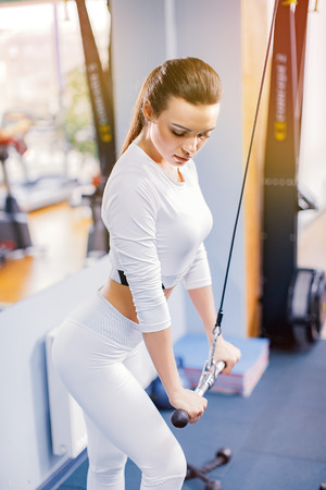 Fit well-trained woman workout triceps lifting weights in gym