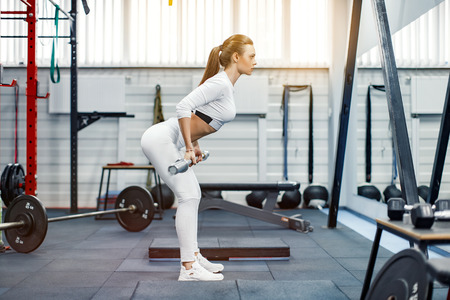 Young fitness woman lifting a weight in the gym. Fitness woman deadlift barbell. Stock Photo