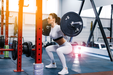 Fit beautiful girl doing squats with barbell in gym. The development of leg muscles, strengthening of the spine after injuries Archivio Fotografico