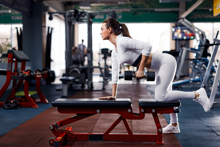 The girl in the gym crouches with a barbell, in a beautiful white sports uniform in gym.