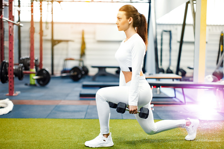 The girl in the gym crouches with a barbell, in a beautiful white sports uniform In the gym, exercises for the development of the muscles of the legs and back.