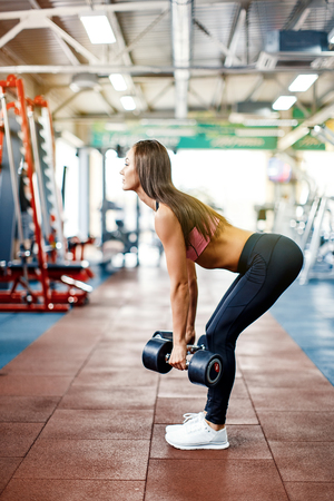The girl in the gym crouches with a barbell. Young Woman training back.