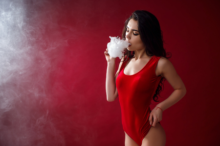 Young sexy woman in red body is vaping. A cloud of vapor. Studio shooting. Archivio Fotografico