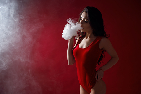 Young sexy woman in red body is vaping. A cloud of vapor. Studio shooting. Stock Photo