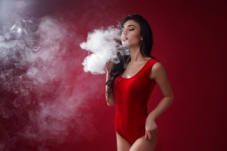 Young sexy woman in red body is vaping. A cloud of vapor. Studio shooting. Banque d'images
