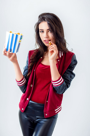Alluring young brunette in popcorn bag looking playfully at camera having bite on white or gray background. Stock Photo