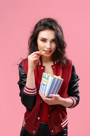 Alluring young brunette in popcorn bag looking playfully at camera having bite on pink background.