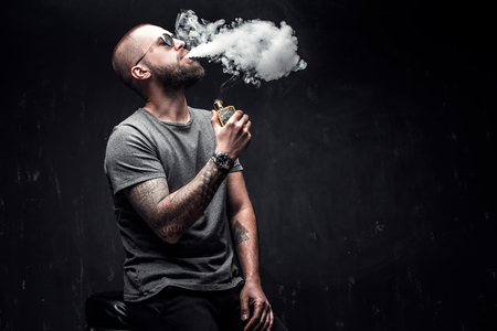 Men with beard in sunglasses vaping and releases a cloud of vapor on dark moody studio background.