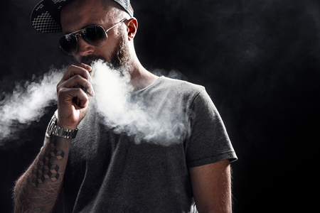 Pensive Black bearded male dressed in a grey shirt, sunglasses and baseball cap vaping. man in holding a mod. A cloud of vapor. Black background. Stockfoto